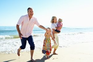 Familia feliz corriendo en la playa